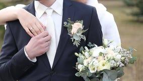 Gifta sig par, den härliga unga bruden och brudgumanseende i en parkera arkivfilmer