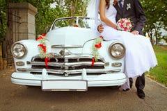 Gifta sig par med bröllopbilen Royaltyfri Bild