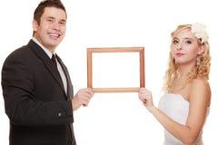 Gifta sig par med den tomma ramen för foto Arkivbild