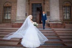 Gifta sig par nära en kyrka Att gifta sig par är att krama sig Skönhetbrud med brudgummen Royaltyfri Foto
