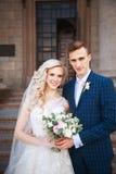 Gifta sig par nära en kyrka Att gifta sig par är att krama sig Skönhetbrud med brudgummen Arkivfoton
