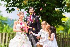 Gifta sig par och brudtärnan som duschar blommor Royaltyfri Foto