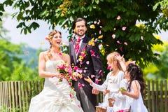 Gifta sig par och brudtärnan som duschar blommor Royaltyfria Bilder