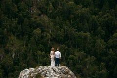 Gifta sig par på kanten av berget royaltyfria bilder