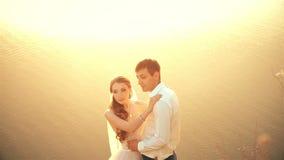 Gifta sig par på stranden på solnedgången arkivfilmer