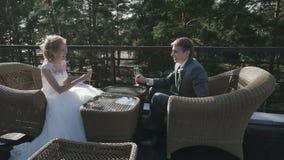 Gifta sig par som dricker champagne på det utomhus- kafét på den seafrontthebruden och brudgummen som dricker champagnesammanträd arkivfilmer