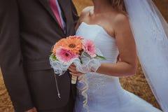 Gifta sig par som kramar, bruden som rymmer en bukett av blommor i hennes hand, brudgummen som omfamnar henne Royaltyfria Bilder