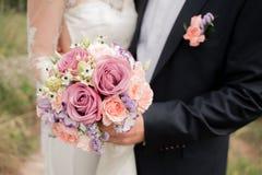 Gifta sig par som kramar, bruden som rymmer en bukett av blommor i hennes hand, omfamna för brudgum Arkivbilder