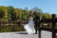 Gifta sig par som kramar och kyssa Mycket härligt bröllop av att förbluffa par arkivbild