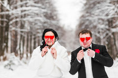 Gifta sig par som poserar med pinnehjärtor, maskering Arkivfoton