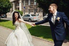 Gifta sig par som rymmer sig parkera in, gränden Arkivfoton