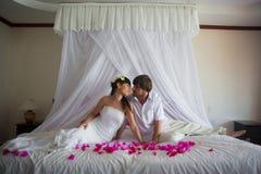 Gifta sig sitter par bredvid de och att vila på en säng royaltyfria foton