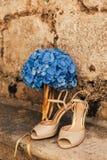 Gifta sig skor av en brud på en stenbakgrund och en blå brud- bukett Royaltyfri Bild
