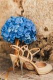 Gifta sig skor av en brud på en stenbakgrund och en blå brud- bukett Royaltyfri Fotografi