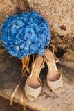 Gifta sig skor av en brud på en stenbakgrund och en blå brud- bukett Royaltyfri Foto