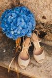 Gifta sig skor av en brud på en stenbakgrund och en blå brud- bukett Arkivbilder