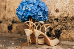 Gifta sig skor av en brud på en stenbakgrund och en blå brud- bukett Fotografering för Bildbyråer
