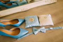 Gifta sig skor av en brud på en stenbakgrund och en blå brud- bukett Royaltyfria Bilder
