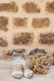 Gifta sig skor av en brud på en stenbakgrund och en vit brud- bukett Royaltyfri Bild