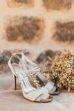Gifta sig skor av en brud på en stenbakgrund och en vit brud- bukett Royaltyfria Foton