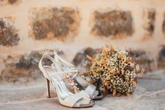 Gifta sig skor av en brud på en stenbakgrund och en vit brud- bukett Arkivbilder