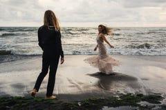 Gifta sig som är lovestory, precis gift par nära havet på solnedgången royaltyfri foto