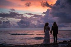 Gifta sig som är lovestory, precis gift par nära havet på solnedgången royaltyfria bilder