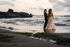 Gifta sig som är lovestory, precis gift par nära havet på solnedgången arkivbilder