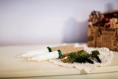 Gifta sig stearinljus dekorerade med gröna band, butonyer för brudgummen, morgon för brud` s Arkivbilder