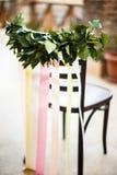 Gifta sig stol dekoreras med gröna sidor och färgade band Royaltyfri Foto