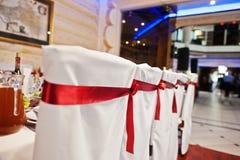 Gifta sig stolar för gäster med röda band Fotografering för Bildbyråer