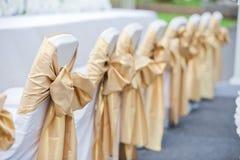 Gifta sig stolar i rad dekorerade det guld- färgbandet Royaltyfria Foton