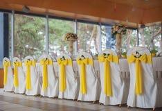 Gifta sig stolar i rad dekorerade med det guld- färgbandet Fotografering för Bildbyråer