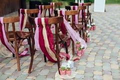 Gifta sig stolar med band, bröllopceremoni i yttersida rustikstil Vit dörrbåge i grön trädbakgrund Fotografering för Bildbyråer