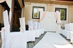 Gifta sig stolar med rosa pilbågar på platsbröllopceremoni Royaltyfri Fotografi