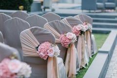 Gifta sig stolar som dekoreras med buketter av blommor Fotografering för Bildbyråer