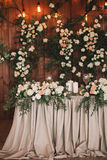 Gifta sig tabellbanketten som dekoreras med blommor och växter, retro lampor på en träbakgrund royaltyfri fotografi