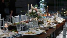 Gifta sig tabellbankettkorridoren av restaurangen som dekoreras med stearinljus och blommor lager videofilmer