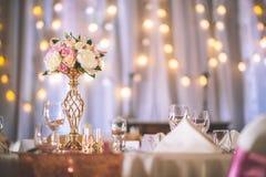Gifta sig tabellen med den exklusiva blom- ordningen som är förberedd för mottagande-, bröllop- eller händelsehöjdpunkt i rosa gu royaltyfri fotografi