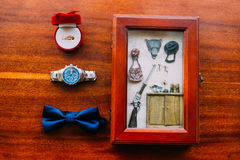 Gifta sig uppsättningen av klockan och flugan för man` s den stilfulla på en brun träbakgrund med guld- cirklar och vykortet i la Royaltyfria Foton