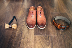 Gifta sig uppsättningen av mäns stilfulla skor, träfluga och bälte på en träbakgrund Royaltyfri Fotografi