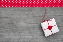 Giftbox обернуло в бумаге при красный цвет услышанный на деревянной предпосылке Стоковое фото RF