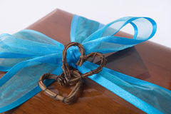 Giftbox. Wooden giftbox with bow and two hearts Royalty Free Stock Photo