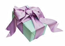 Giftbox. Gift box wrapped with wrapping tissue and a satin bow isolated on a white background Stock Photography