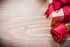 Giftbox avec l'arc attaché augmenté s'est levé sur le copyspace de conseil en bois Photo libre de droits