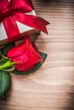 Giftbox avec l'arc attaché s'est levé sur la vue supérieure de conseil en bois Images stock