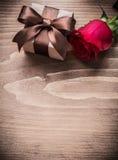 Giftbox avec la rose de rouge d'arc sur le concept de vacances de conseil en bois Photo stock