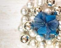Giftbox blu circondato dalle bagattelle d'argento Fotografia Stock