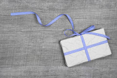 Giftbox with blue striped ribbon on a grey wooden background Royalty Free Stock Photos
