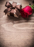 Giftbox with bow red rose on wooden board holiday concept Stock Photo